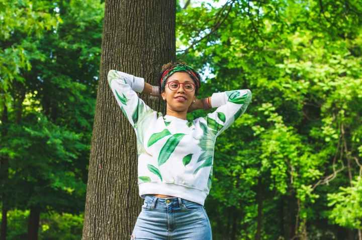 woman wearing green and white floral long sleeved laying on tree bark